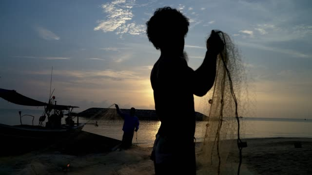 silhouette of fishermen with yellow sun rise in the background. - fisherman stock videos & royalty-free footage