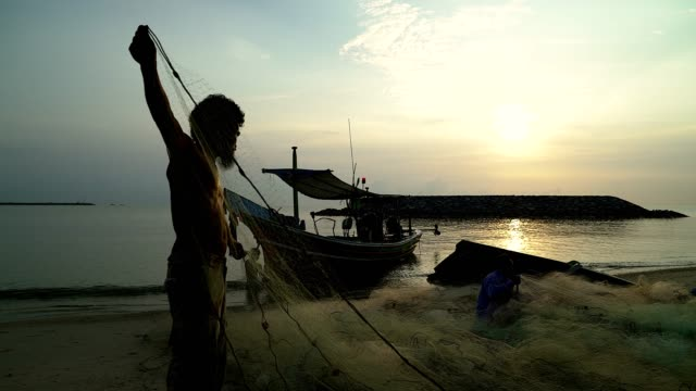 Silhouette of fishermen with yellow sun rise in the background.