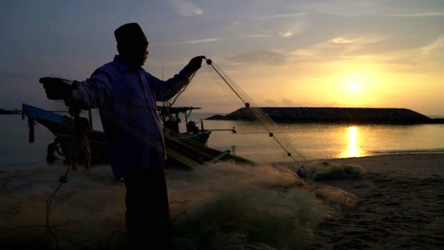 silhouette of fishermen with yellow sun rise in the background. - fishing net stock videos & royalty-free footage
