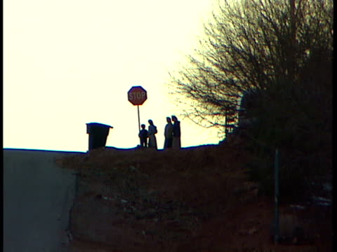 silhouette of four children one boy three girls standing at top of hill w/ almost silhouette of red stop sign silhouette of garbage can of sign... - one tree hill stock videos and b-roll footage