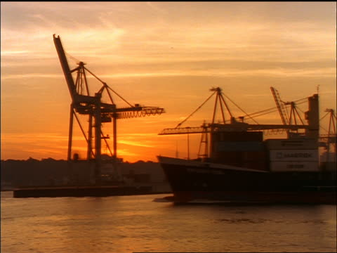 silhouette of freighter passing shipping port at sunset / zoom in at end / hamburg harbor, germany - anno 1998 video stock e b–roll