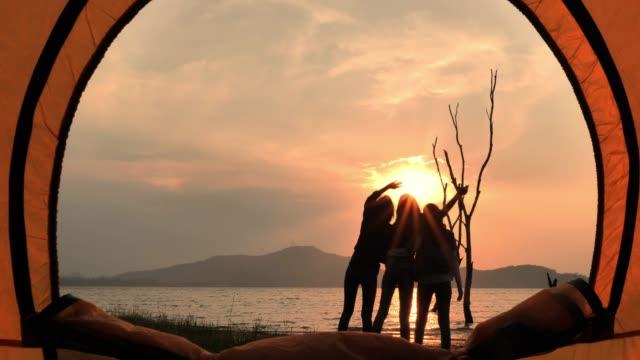 vídeos de stock, filmes e b-roll de silhueta dos amigos que acampam bebendo, acampando, férias de verão e conceito das férias. camping - sombra