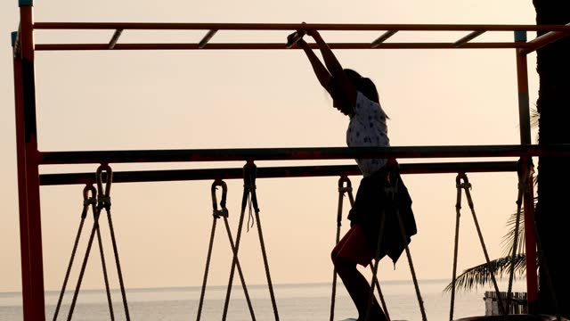 silhouette of girl playing at climbing equipment in the morning near the beach, lifestyle concept. - climbing equipment stock videos & royalty-free footage