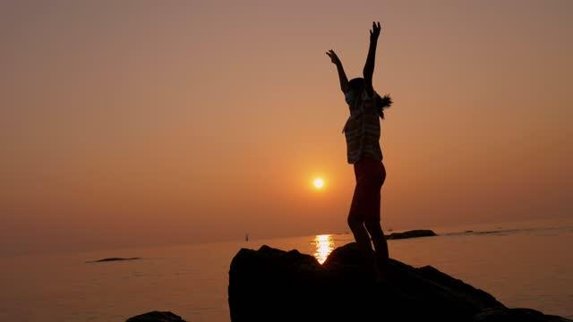 vídeos de stock, filmes e b-roll de silhueta de menina em pé na rocha e levantando as mãos na praia com o nascer do sol pela manhã, conceito de estilo de vida. - braço humano