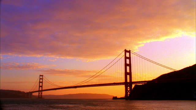 t/l, ws, silhouette of golden gate bridge against moody sky at sunset, san francisco, california, usa - golden gate bridge stock videos & royalty-free footage
