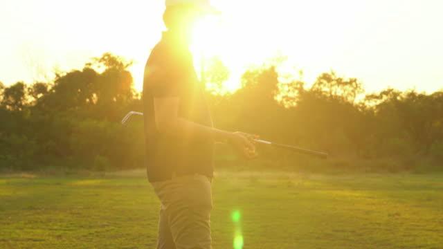 silhouette of golfer walking along fairway - golf swing silhouette stock videos & royalty-free footage