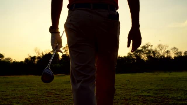 フェアウェイに沿って歩くゴルファーのシルエット - ゴルフのティー点の映像素材/bロール