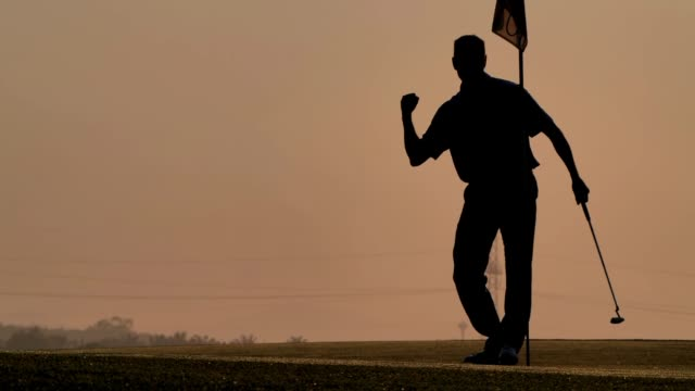 silhouette of golfers hit sweeping and keep golf course in the summer for relax time.silhouette golfer at sunset.male golfer happy for successful putt on the green.sports cinemagraphs - golf stock videos & royalty-free footage