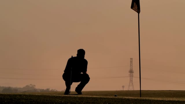 silhouette of golfers hit sweeping and keep golf course in the summer for relax time.silhouette golfer at sunset - golf swing silhouette stock videos & royalty-free footage