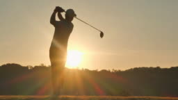 Silhouette of golfers hit sweeping and keep golf course in the summer for relax time.Silhouette golfer at sunset.4K Sports