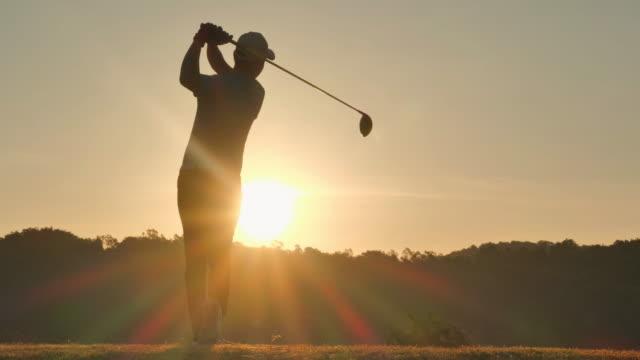 ゴルファーのシルエットは、スイープをヒットし、リラックスした時間のために夏にゴルフコースを維持します。夕暮れ時のシルエットゴルファー.4kスポーツ - ゴルフ点の映像素材/bロール