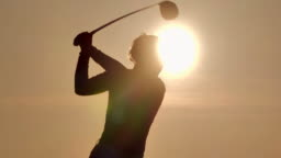Silhouette of golfers women hit sweeping and keep golf course in the summer for relax time.Silhouette golfer at sunset.Sports Cinemagraphs.Confidence,Power,Skill,Strength,Success.Women in Sport