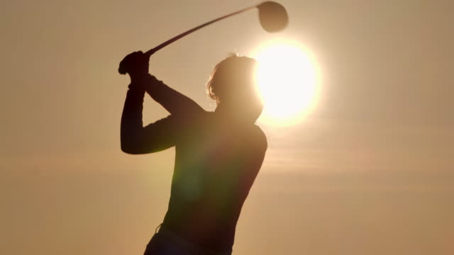vidéos et rushes de silhouette de golfeurs femmes frappé balayage et garder le terrain de golf en été pour se détendre. golfeur de silhouette au coucher du soleil. sports cinemagraphs.confidence,power,skill,strength,success.women in sport - golf