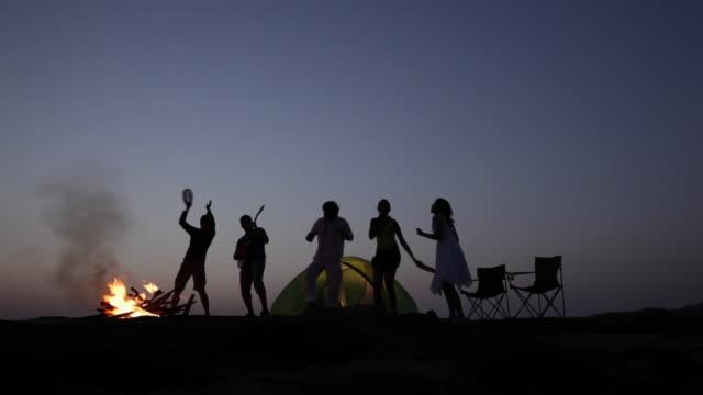 vídeos y material grabado en eventos de stock de silhouette  of group of friends dancing  - guitarra