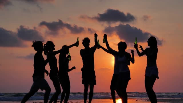 vídeos de stock e filmes b-roll de silhouette of group of friends having fun on the beach and drinking alcohol.vacations - istock - festa