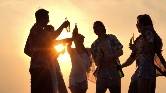 vídeos de stock e filmes b-roll de silhouette of group of friends having fun on the beach and drinking alcohol.slow motion.vacations concept. - beer alcohol