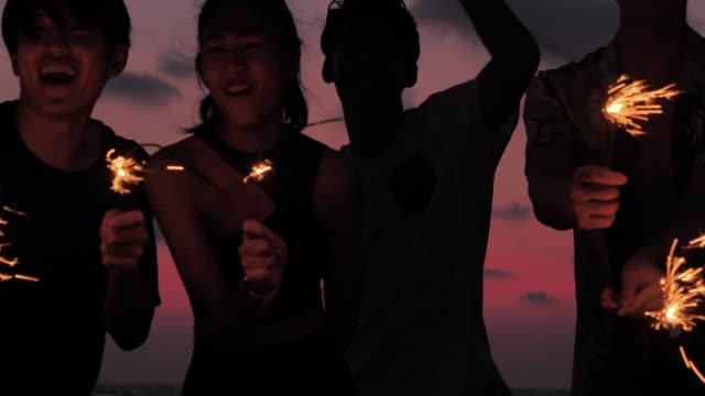 vídeos de stock, filmes e b-roll de silhueta do grupo de amigos que têm o divertimento na praia com sparklers, vacations-istock - dançar em discoteca