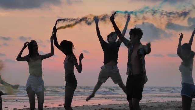 silhouette of group of friends having fun on the beach with sparklers - thailand stock videos & royalty-free footage