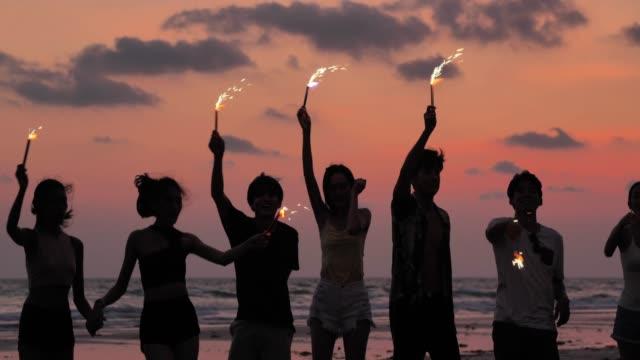 花火とビーチで楽しんでいる友人のグループのシルエット - タイ王国点の映像素材/bロール