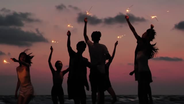 vídeos de stock e filmes b-roll de silhouette of group of friends having fun on the beach with sparklers - festa