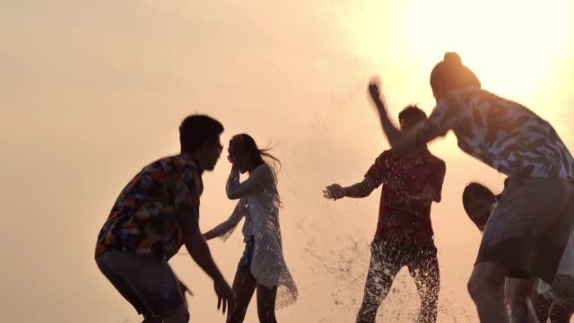 silhouette of group of friends having fun on the beach.slow motion.vacations - holiday event stock videos & royalty-free footage