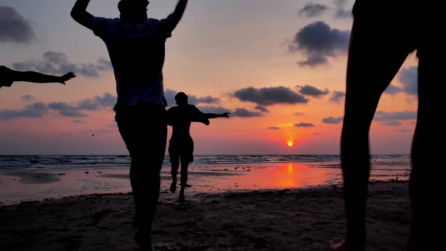 silhouette of group of friends having fun running on the beach,vacations - istock - adult stock videos & royalty-free footage