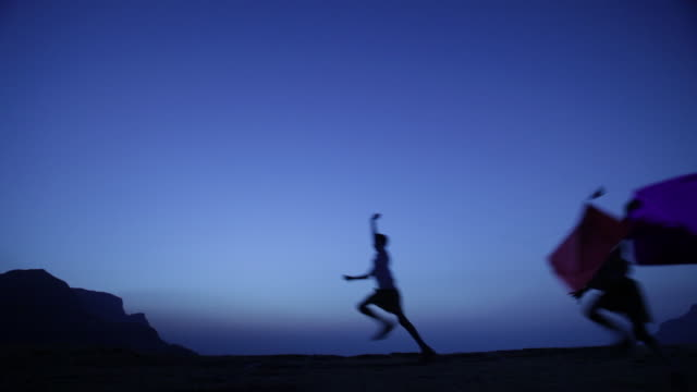 silhouette of group of kids running on the cliff of mountain  - vignette stock videos & royalty-free footage