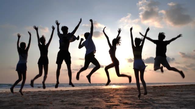 夏のビーチで一緒に跳躍笑顔の友人のグループのシルエット, 友情, 海, 夏休み, 休日と人々の概念, 休暇-istock - タイ王国点の映像素材/bロール
