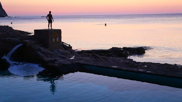 Silhouette of guy contemplating and taking pictures with smartphone of the sunrise from the Mediterranean Sea Costa Brava shoreline in a stunning outdoor and beautiful colors.
