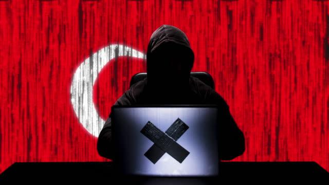 ハッカーのシルエットは、背景にトルコの旗を持つ彼のラップトップ上のコードハッキングを入力します - アノニマス点の映像素材/bロール