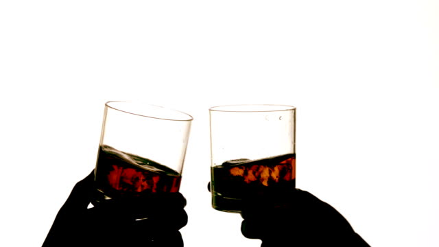 Silhouette of hands clinking whiskey glasses
