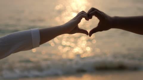 silhuetten av händerna älskare på stranden vid solnedgången tid göra hjärta form, kärlek och bröllop koncept, 4k(uhd) - välbefinnande bildbanksvideor och videomaterial från bakom kulisserna