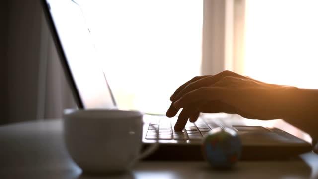 Silhouet van handen op het toetsenbord van moderne laptop