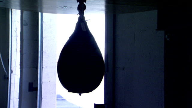 silhouette of hanging speed bag fg, almost silhouette of coiling garage door sliding down, closing, blocking out outdoor light. training, sports,... - punch bag stock videos & royalty-free footage