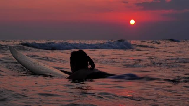 vídeos y material grabado en eventos de stock de silueta de la hermosa chica surfista sexy en la tabla de surf y esperando las olas. en la playa al atardecer. deportes cinemagraphs, vacations-istock - esperar