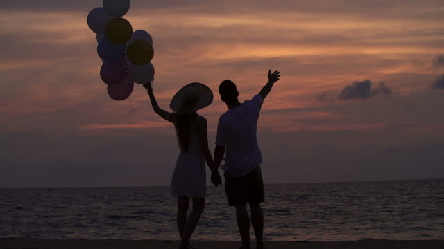 Silhouette of happy couple having fun together at the beach