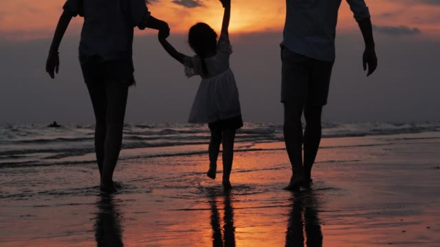 silhouette of happy family walking together on the beach.happy family enjoy summer vacation on the beach.vacations - istock - isole del pacifico video stock e b–roll