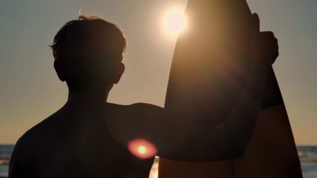silhouette of happy senior male surfer standing with surfboard on the beach.real bodies - active seniors stock videos & royalty-free footage
