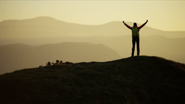 silhouette of hiker celebrating success at sunrise snowdonia - northern europe stock videos & royalty-free footage