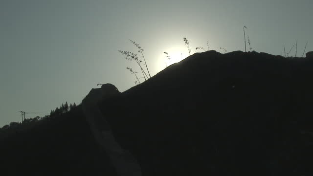 CU Silhouette of hill with grass backlit by sun, Huanghua, China