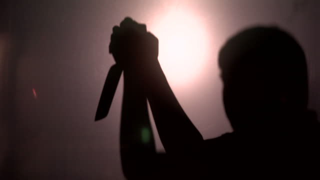 silhouette of horror man and beating knife in hand - knife crime stock videos & royalty-free footage