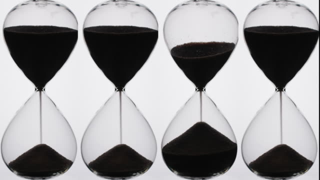silhouette of hour glass timers. - timer stock videos and b-roll footage