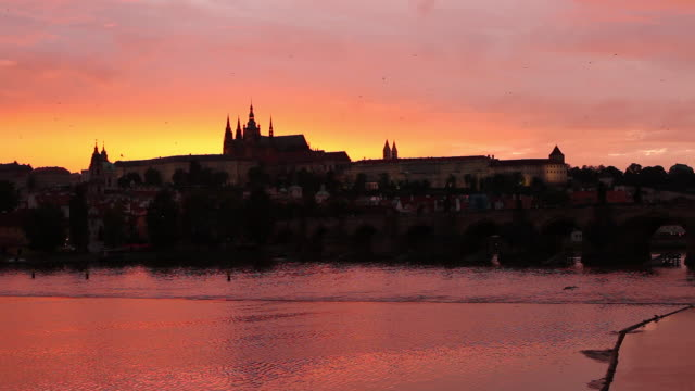 ws silhouette of hradcany castle across vltava river at sunset / prague, czech republic - river vltava stock videos & royalty-free footage