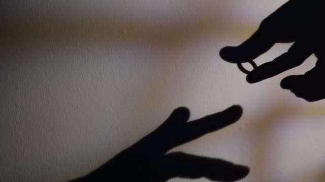 silhouette of  human hand with an engagement ring that will put it on the ring finger of his beloved. - human finger stock videos & royalty-free footage
