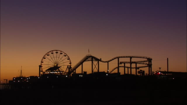 silhouette of illuminated ferris wheel and roller coaster at santa monica pier. - ferris wheel stock videos & royalty-free footage
