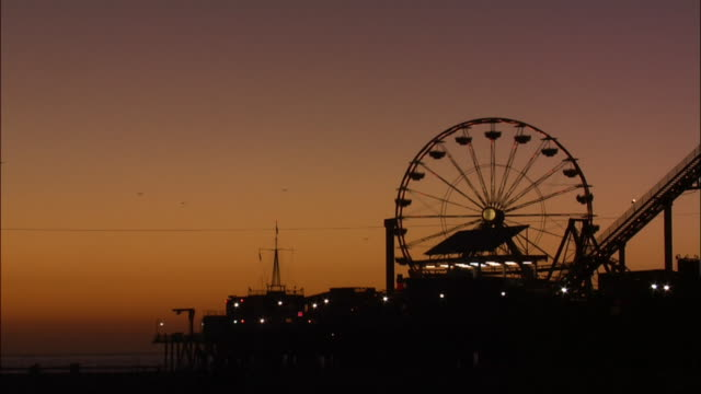 silhouette of illuminated ferris wheel at santa monica pier. - ferris wheel stock videos & royalty-free footage