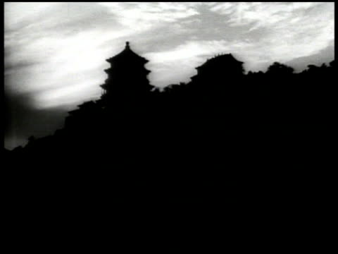 silhouette of japanese buildings, pagoda, on hill. people walking in public square. waterfront w/ modern building bg, trees & branches hanging fg. - pagoda点の映像素材/bロール