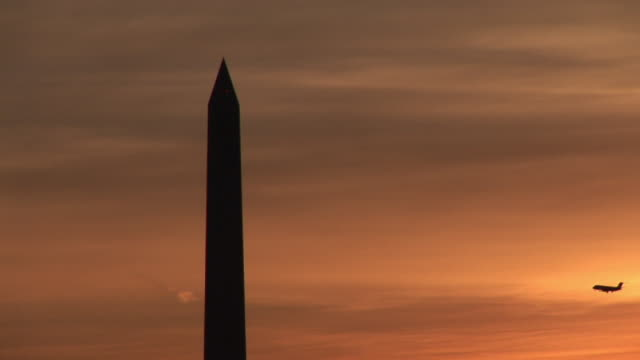 vidéos et rushes de ms, silhouette of jet flying by washington monument at sunset, washington dc, washington, usa - obelisk