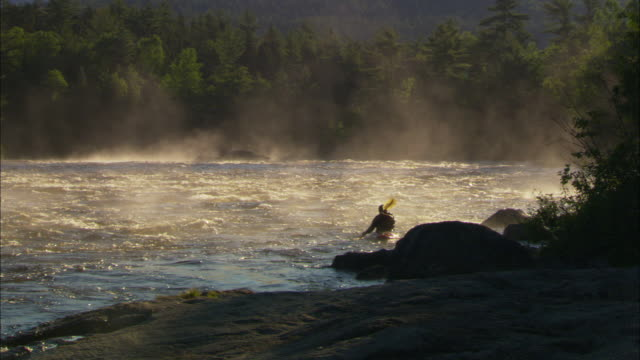 vídeos de stock e filmes b-roll de ms, silhouette of kayaker paddling up stream, mist rising from water, cribworks rapids on penobscot river, maine, usa - remar com remo