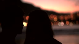 Silhouette of loving couple kissing on the beach